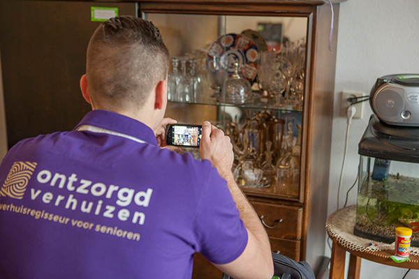 Verhuisregisseur Ontzorgd Verhuizen neemt foto van inhoud van de kast